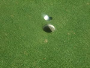 Golf ball approaches hole
