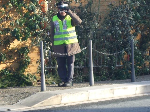 Man in cap and green vest, with binoculars.