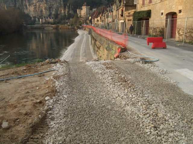 Stone is being put down between the road and the river.