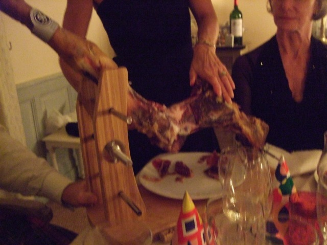 Carving slivers of Spanish ham at the table.