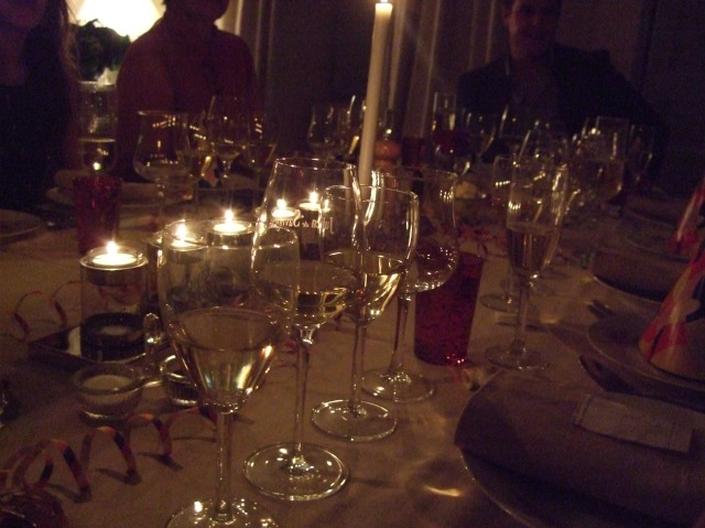 Glasses glinting in the candles' glow.