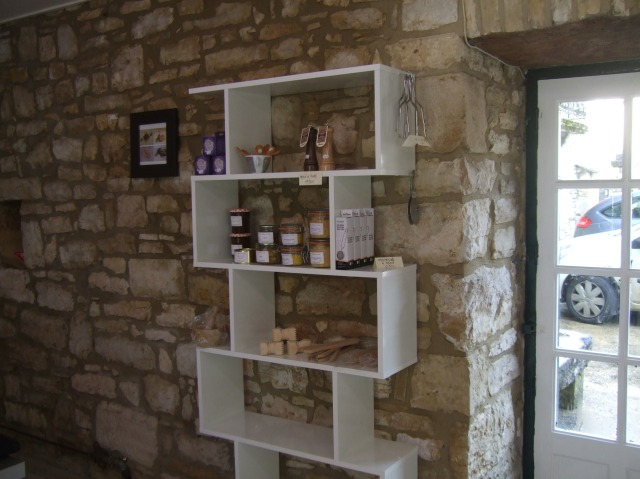 Shelving unit with patés and various kitchen tools.