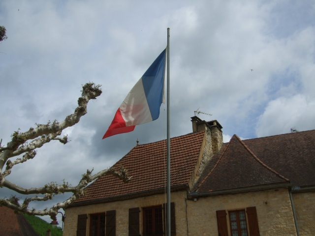 The French flag against a cloudy May sky in Daglan.