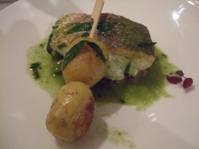 Nicely cooked fish with potatoes on a wooden skewer.