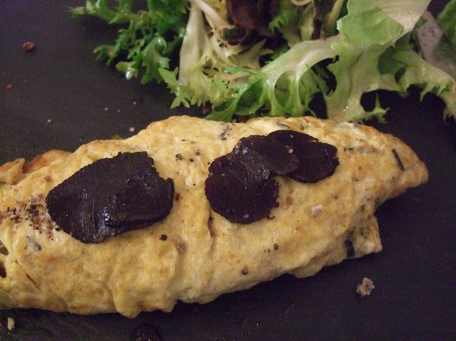 Thin slices of black truffle decorate the top of the omelette.