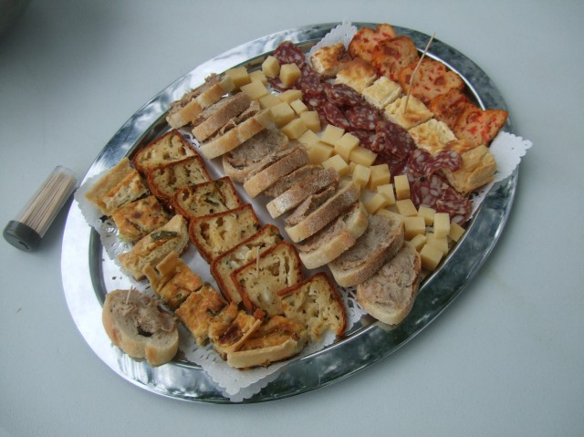 A tray with a variety of breads and other goodies.