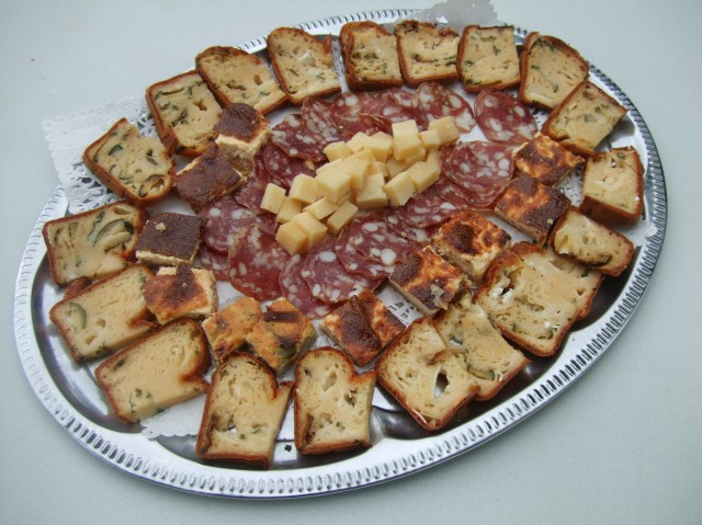 A tray of sausages, ringed by slices of special breads.
