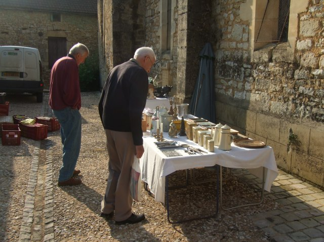 Two shoppers examine the goods on tables behind the church.