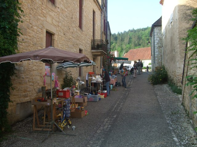Tables are being stocked with goods, on the road up to the main square.
