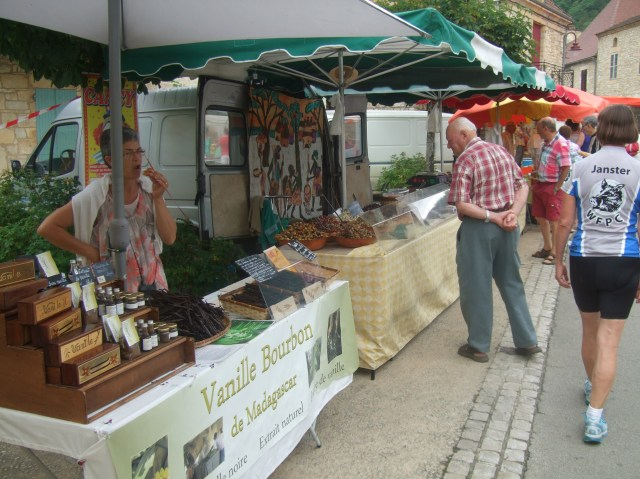 In the foreground, a stand selling vanilla beans.