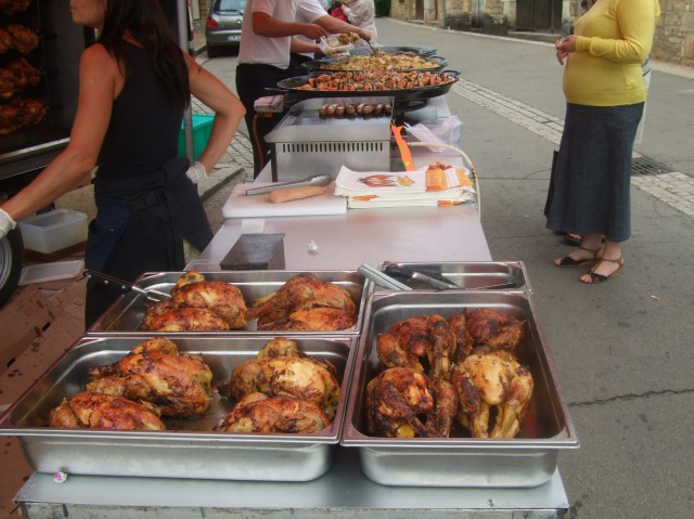 A long row of hot prepared foods, starting with roast chickens.