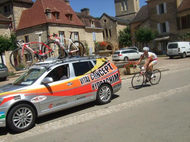 The very last racer follows a team car through the village square.