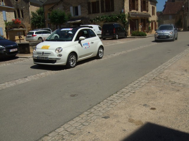 An official car of the Tour de Dordogne moves through the village.