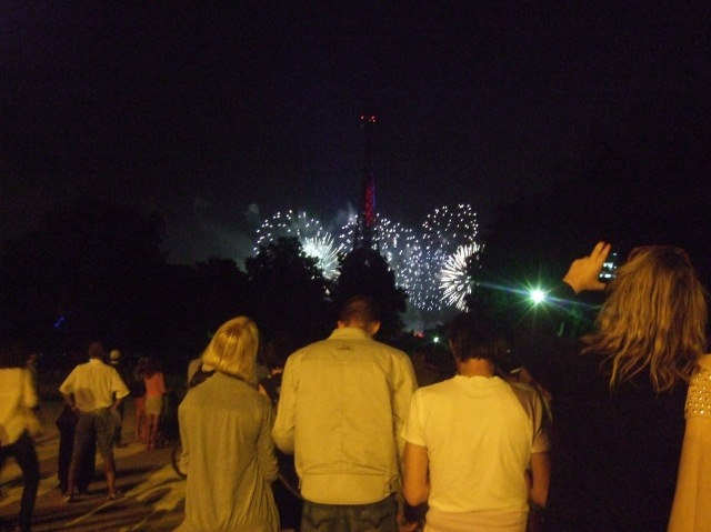 On the Champ-de-Mars, the crowd watches the Tower and the fireworks.
