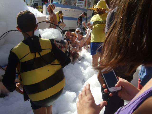 One of the honey bees enjoys the foam, along with the crowd.