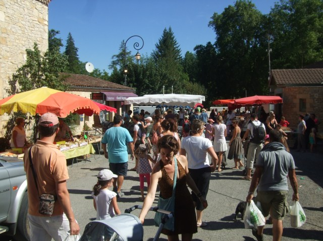 Tourists and residents arrive at Daglan's weekly market, in a new location.