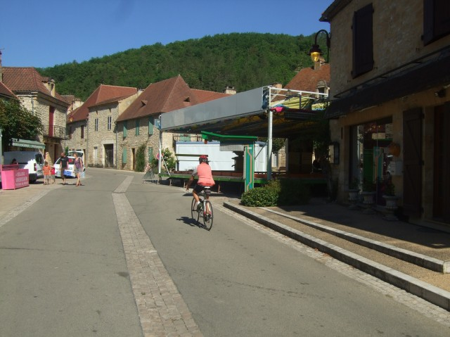 A cyclist heads into Daglan's main square, with the bumper-car ride on the right.