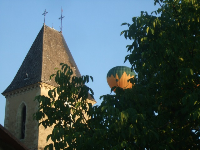 A balloon peeks over a walnut tree and heads for the church tower.
