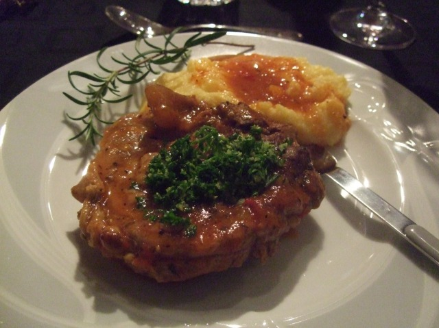 A serving of osso buco, with polenta and sauce.
