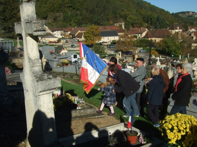 A young girl has the honour of placing some flowers on a memorial.