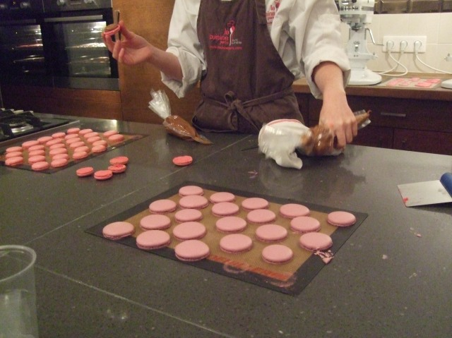 Our instructor shows how to pipe the filling onto the bottom cookie.