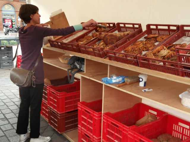 A vendor picks out breads for a customer in Toulouse.