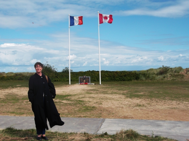 The flags of France and Canada wave over the beach.