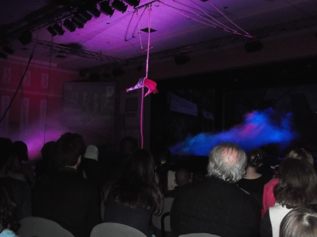 An acrobat swings over the audience at the resort's theatre.
