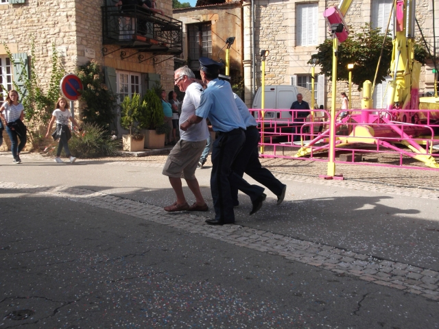 One of the parade viewers is grabbed, taken away, and placed in the gendarmes' car.