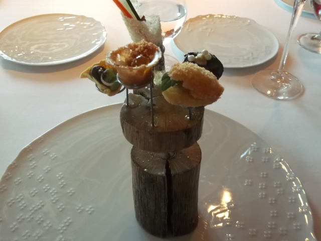 Several amuse-bouches, perched on a wooden base.