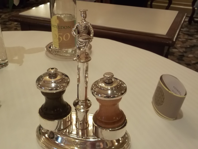 Below? Salt and pepper. Above? Another figure of Paul Bocuse.